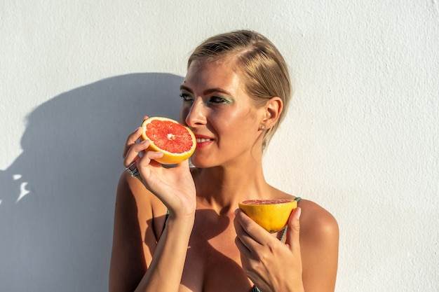 Красивая молодая женщина в купальнике с грейпфрутом.