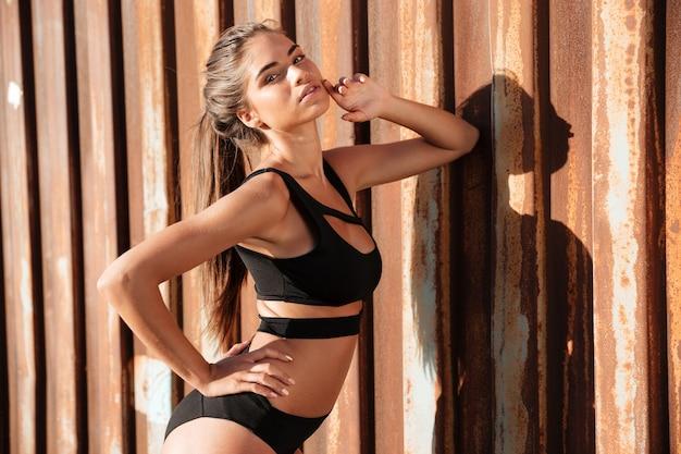녹슨 금속 벽에 수영복에 아름 다운 젊은 여자