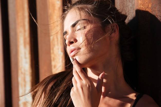 さびた金属の壁の上の水着の美しい若い女性