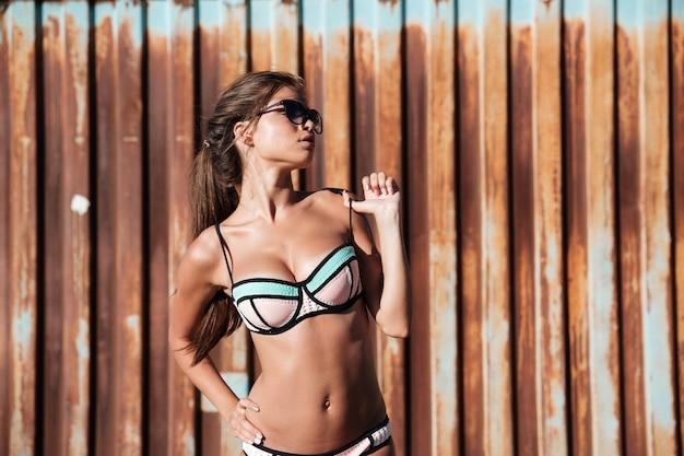さびた金属の壁の上に立ってポーズをとって水着の美しい若い女性