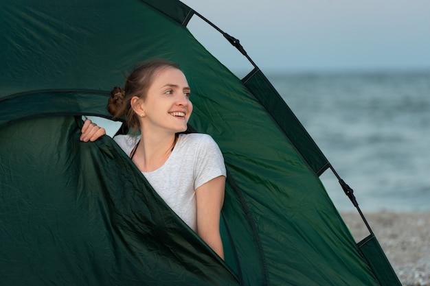 ちょうどビーチの砂の上にテントキャンプで美しい若い女性。テントの中で微笑んでいる女の子。
