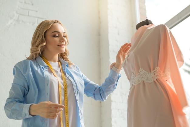 직장에서 아틀리에에서 아름 다운 젊은 여자는 마네킹에 드레스를 만든다