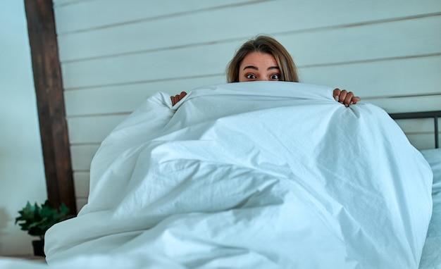 Красивая молодая женщина в постели. девушка с открытыми глазами закрывает лицо белым одеялом утром. не высыпается концепция.