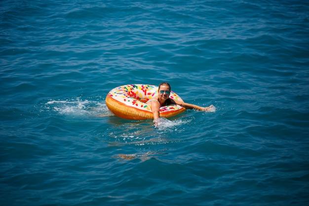Красивая молодая женщина в море плавает на надувном кольце и развлекается на отдыхе. девушка в ярком купальнике у моря под солнечным светом