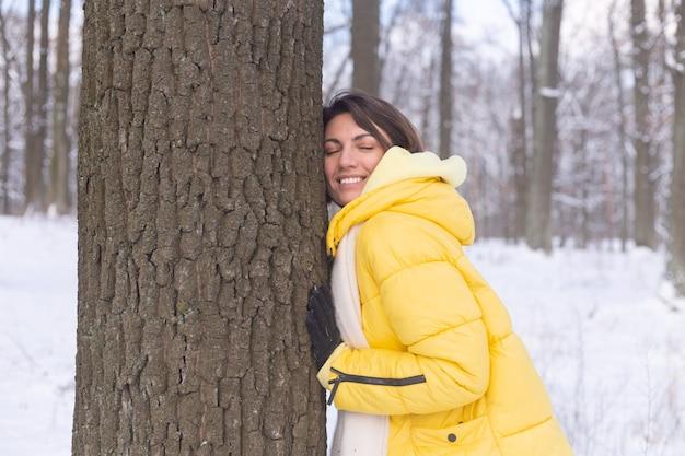 冬の森の美しい若い女性は、自然への優しい気持ちを示し、木への彼女の愛を示しています