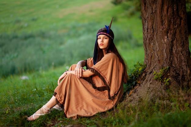 草の上に座って、伝統的なネイティブインディアンのドレスを着た美しい若い女性