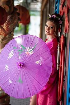 中国の旧正月のお祝いの際に伝統的な東洋の着物のドレスを着た美しい若い女性