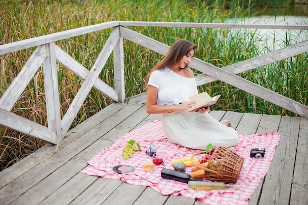 古着の美しい若い女性は、木製の桟橋だけでピクニックをしています。フレンチスタイルの屋外のピクニック