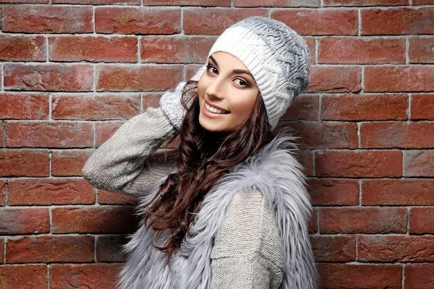 Красивая молодая женщина в теплой одежде, стоя у кирпичной стены