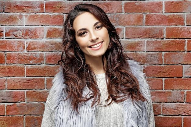 벽돌 벽 근처에 서 있는 따뜻한 옷을 입은 아름다운 젊은 여성