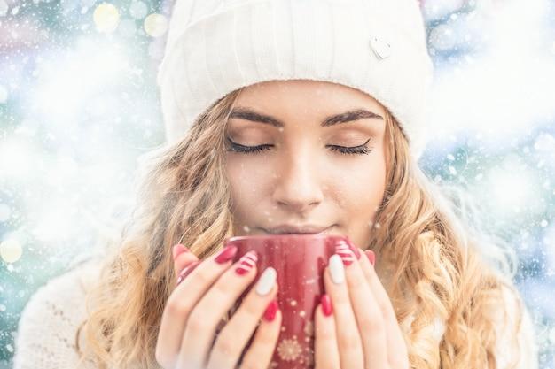 ホットティーコーヒーまたはパンチのカップと暖かい服を着た美しい若い女性。抽象的な冬の雪の天気の肖像画。