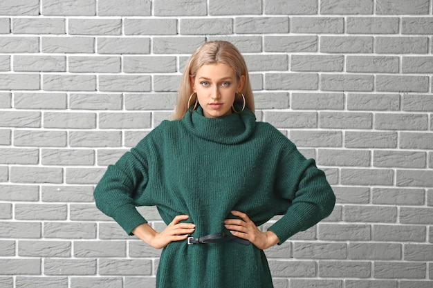 レンガの背景に暖かいセーターの美しい若い女性