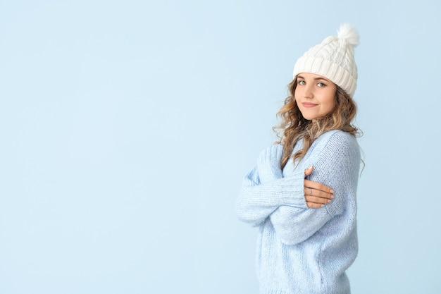 Красивая молодая женщина в теплом свитере на цветном фоне