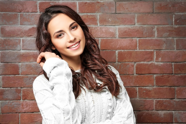벽돌 벽 근처에 서 있는 따뜻한 스웨터를 입은 아름다운 젊은 여성