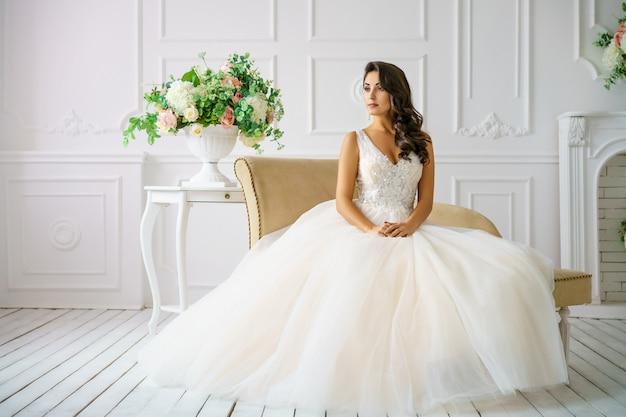結婚式の美しい若い女性は美しい化粧と髪型幸せな花嫁をドレスアップします。