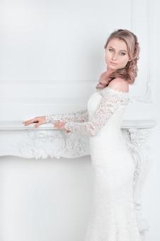 Красивая молодая женщина в свадебном платье стоя в свадебном салоне. праздники и события