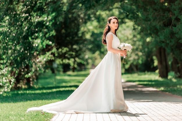 Красивая молодая женщина в свадебном платье, стоя в парке