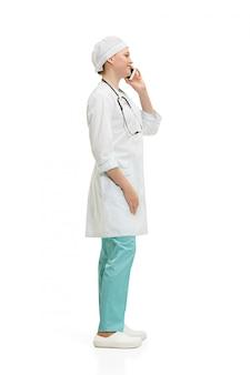 Красивая молодая женщина в белом халате позирует говорить по телефону