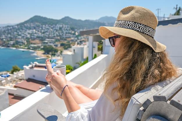 シービューの家やホテルの白いテラスのバルコニーに座っている白いドレスと麦わら帽子とコーヒーカップの美しい若い女性。