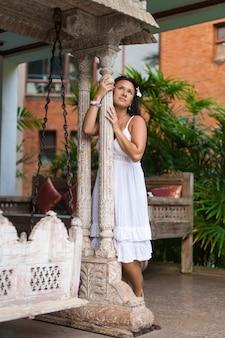 庭でビンテージスイングを夢見ている白いドレスの美しい若い女性。