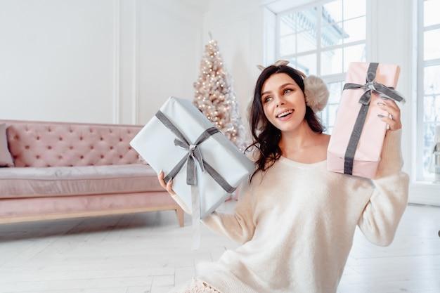 선물 상자와 함께 포즈를 취하는 하얀 드레스를 입고 아름 다운 젊은 여자