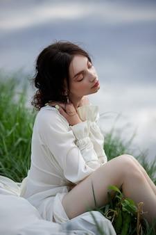 Красивая молодая женщина в белом платье, отдыхая на берегу реки пруд озера. профессиональный макияж и прическа на вьющиеся волосы