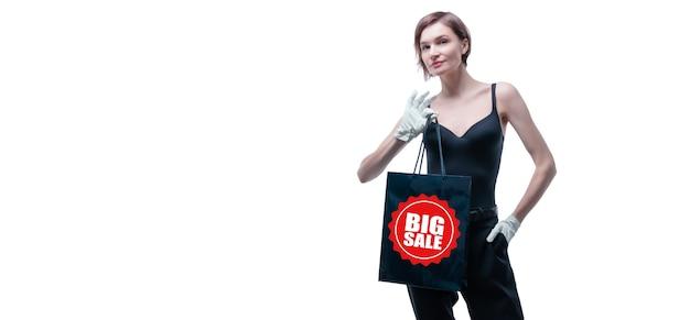 Красивая молодая женщина в белых перчатках держит в руке черную ремесленную сумку