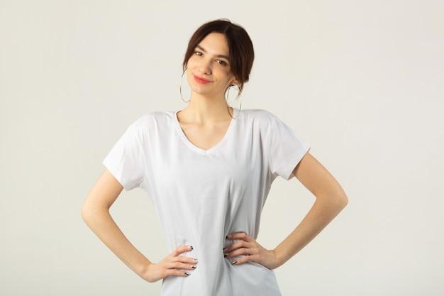 Красивая молодая женщина в белой футболке на белом фоне