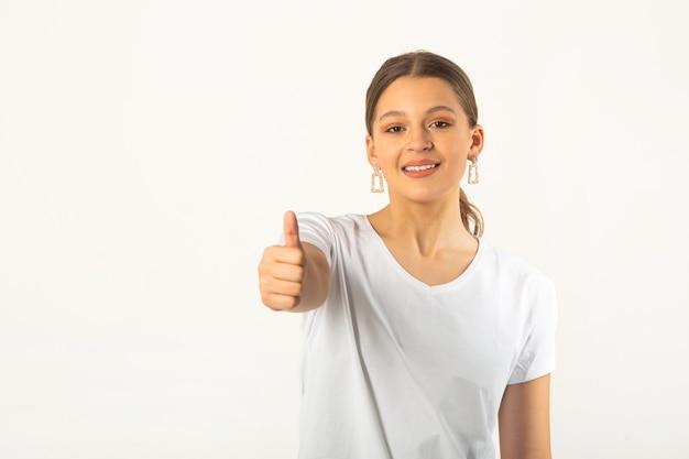 손 제스처와 흰색 배경에 흰색 티셔츠에 아름 다운 젊은 여자