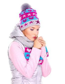 彼女の手を暖める冬の服を着た美しい若い女性