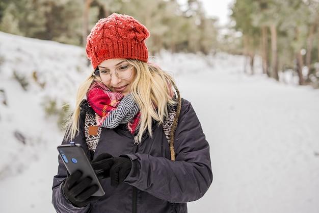 겨울 옷을 입은 아름다운 젊은 여성이 눈과 문자 메시지로 뒤덮인 공원에 서 있습니다.