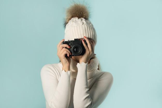 青い背景の手にカメラと冬の帽子の美しい若い女性