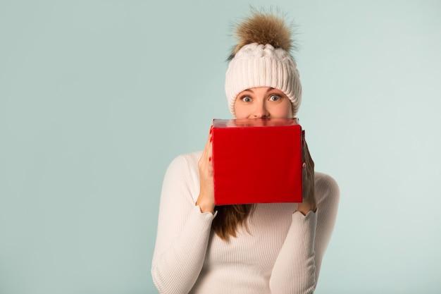 青い背景の手に贈り物と冬の帽子の美しい若い女性