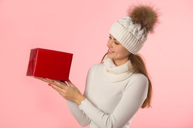 ピンクの背景にギフトを手に冬の帽子の美しい若い女性