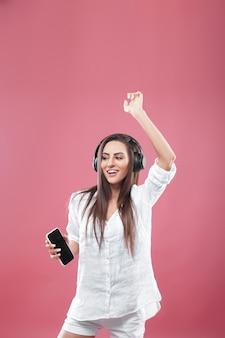 Красивая молодая женщина в беспроводных наушниках, слушать музыку с помощью мобильного телефона