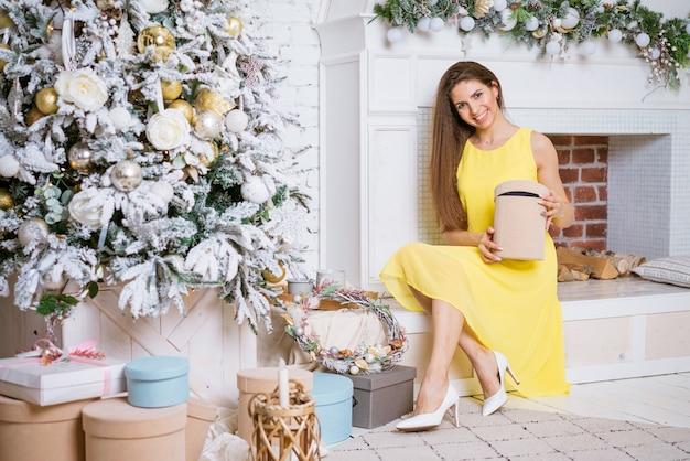 黄色のドレスを着た美しい若い女性は、暖炉のそばのお祝いのクリスマスツリーでプレゼントを保持しています...