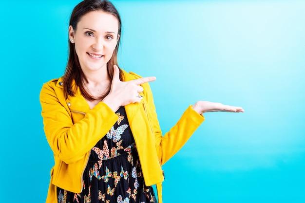 Красивая молодая женщина в желтой куртке на синем фоне, показывая рукой указывая пальцем