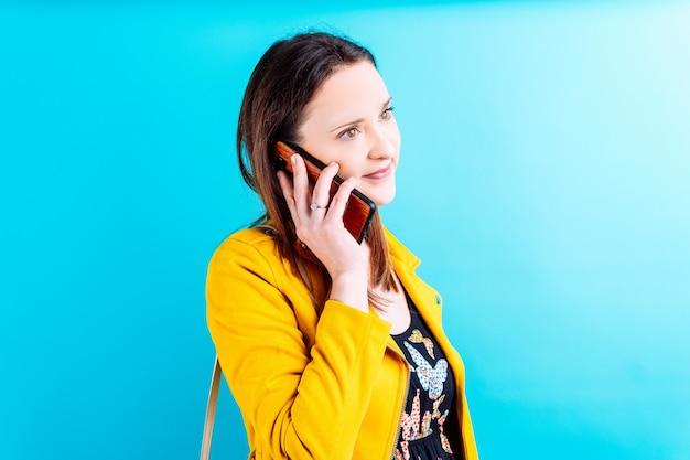 Красивая молодая женщина в желтой куртке на синем фоне разговаривает по телефону. концепция коммуникации и моды