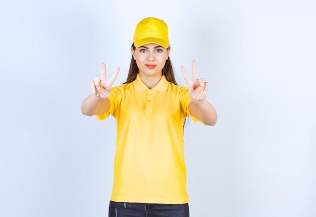 白い背景にサインを与える黄色の衣装で美しい若い女性。