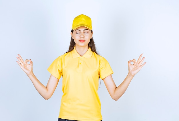 노란색 티셔츠와 모자를 쓴 아름다운 젊은 여성이 흰색 배경에 포즈를 취하고 있습니다.