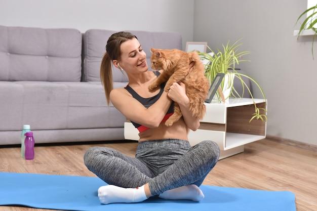 フラットで屋内で赤い猫とポーズをとってヨガの美しい若い女性。