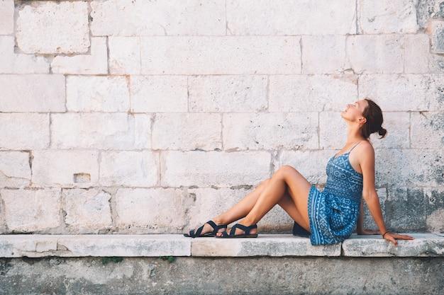 자다르, 크로아티아에서 아름 다운 젊은 여자. 유럽 해안의 여름 휴가. 자다르의 오래된 역사적 거리를 걷고 있는 관광객들. 라이프 스타일, 휴가 및 여행 개념입니다.