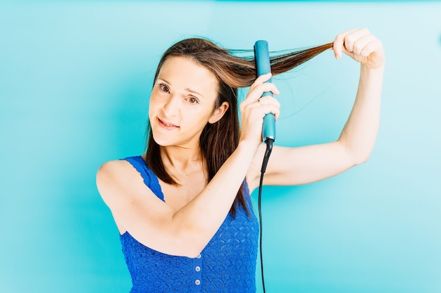 Beautiful young woman ironing her hair with hair straightener on blue background