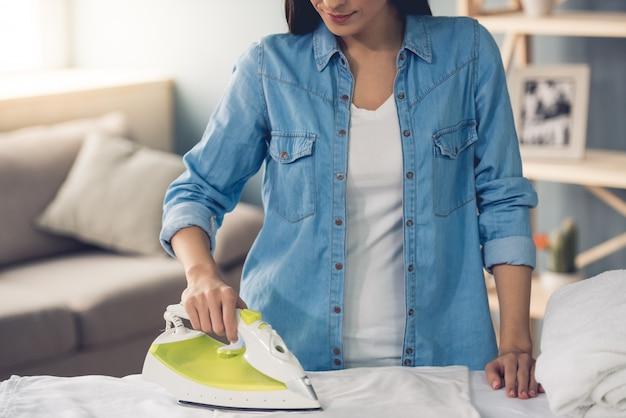 Beautiful young woman ironing at home.