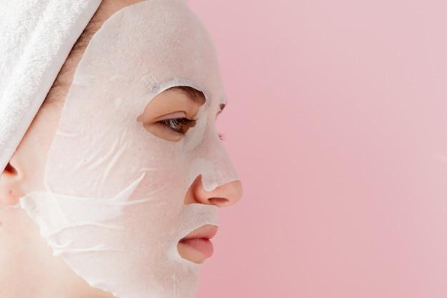 아름 다운 젊은 여자는 분홍색 배경에 얼굴에 화장품 티슈 마스크를 적용하고 있습니다. 건강 관리 및 미용 치료 및 기술 개념