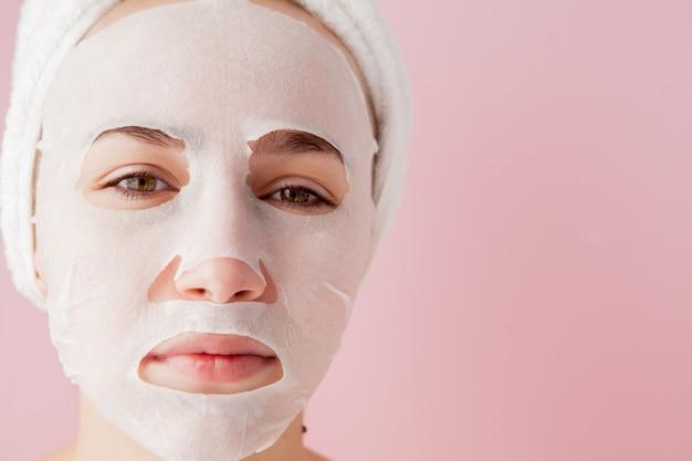 아름 다운 젊은 여자는 분홍색 배경에 얼굴에 화장품 티슈 마스크를 적용