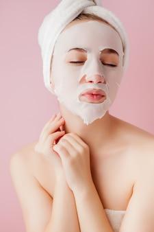 아름 다운 젊은 여자는 분홍색 공간에 얼굴에 화장품 티슈 마스크를 적용합니다