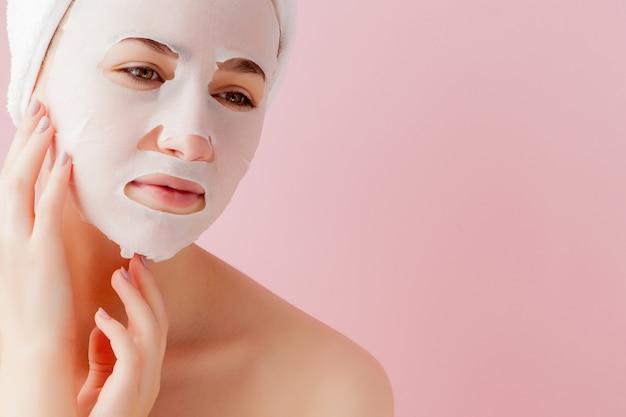 아름 다운 젊은 여자는 분홍색 벽에 얼굴에 화장품 티슈 마스크를 적용하고 있습니다. 의료 및 미용 치료 및 기술 개념.