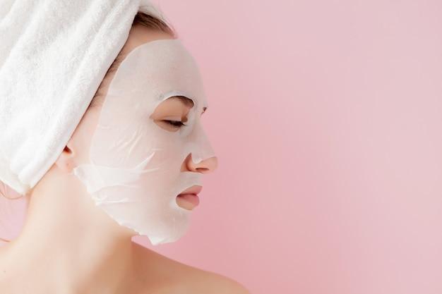아름 다운 젊은 여자는 분홍색 벽에 얼굴에 화장품 티슈 마스크를 적용하고 있습니다.