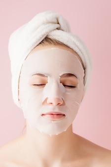 아름 다운 젊은 여자는 분홍색에 얼굴에 화장품 티슈 마스크를 적용하고 있습니다.